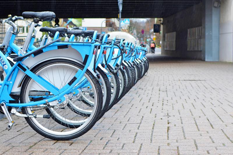 Blauwe tijdelijke huurfietsen van Duitse die vervoervereniging van het gebied Rijn-Neckar 'Nextbike 'op een rij bij parkerensta w royalty-vrije stock afbeeldingen