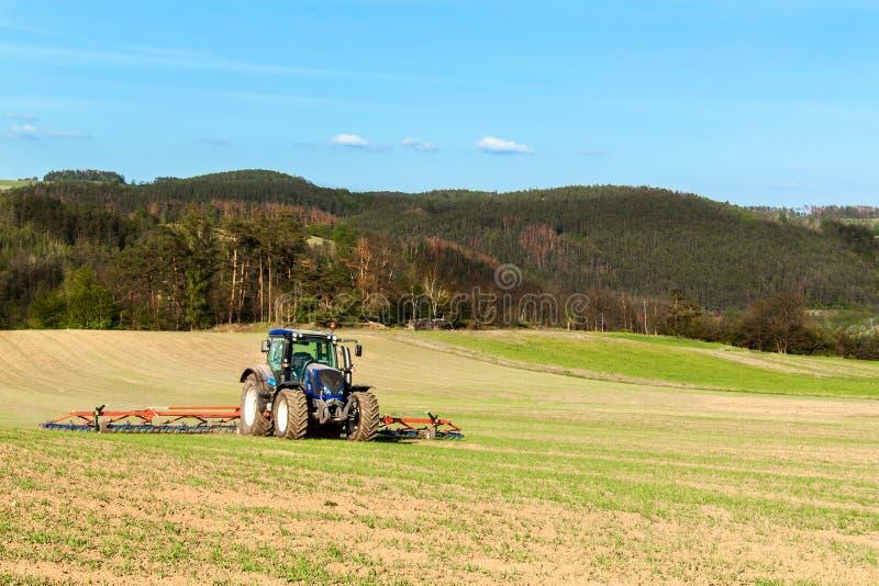 Blauwe tractor op het gebied Het werken aan een landbouwlandbouwbedrijf in de Tsjechische Republiek Het de lentewerk in landbouw stock afbeelding