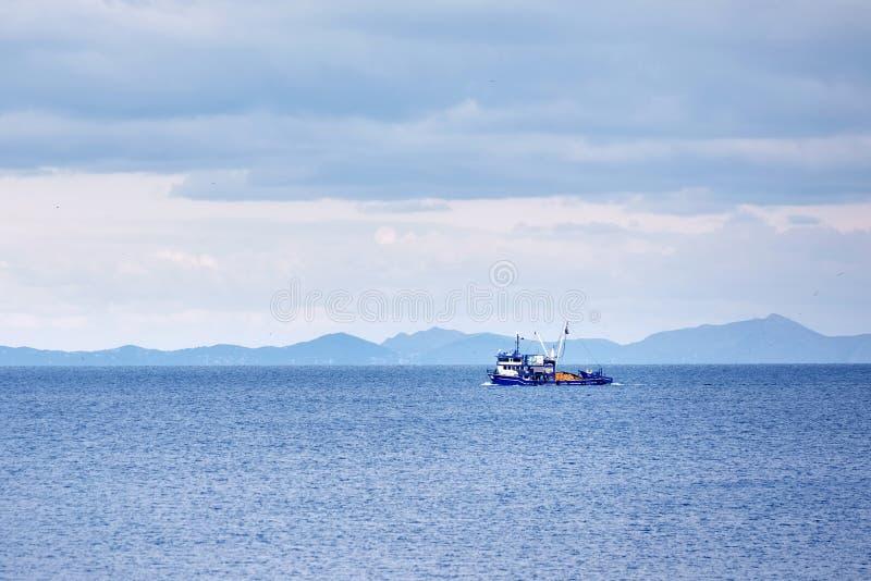 Blauwe treiler vissersboot die over het kalme overzees varen royalty-vrije stock fotografie