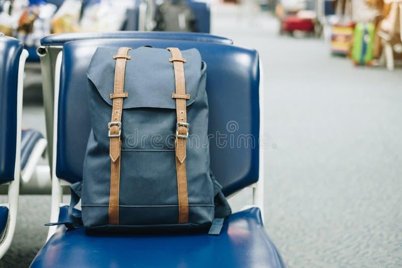 Blauwe uitstekende zak op zetel bij het binnenland van luchthaventerminal Reis en terug naar schoolconcept stock afbeeldingen