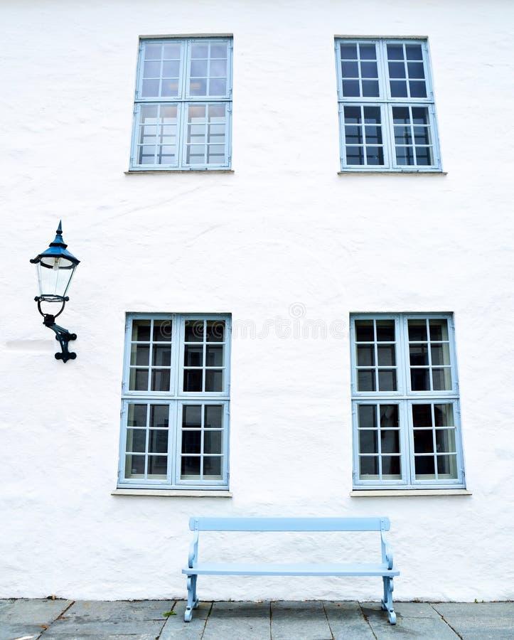 Blauwe vensters, een blauwe bank en een straatlantaarn stock afbeeldingen