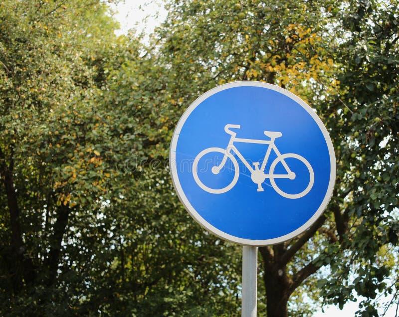 Blauwe verkeersteken voor fietsweg met bomen op achtergrond cycling royalty-vrije stock foto