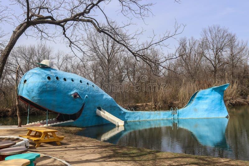 Blauwe vinvis - Uitstekend oud metaal lokaal oriëntatiepunt in zwemmende vijver in openbaar park in Catoosa Oklahoma op iconische royalty-vrije stock afbeelding