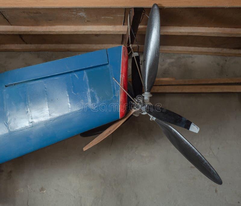 Blauwe vliegtuigvleugel van modelvliegtuigen met propeller het hangen op een houten plank van voertuig spung Propellor en blauw royalty-vrije stock afbeelding