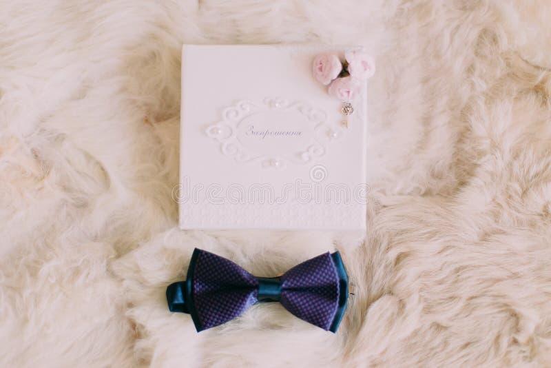 Blauwe vlinderdas en huwelijksuitnodigingskaart met uiterst kleine roze rozen op witte bontachtergrond royalty-vrije stock fotografie