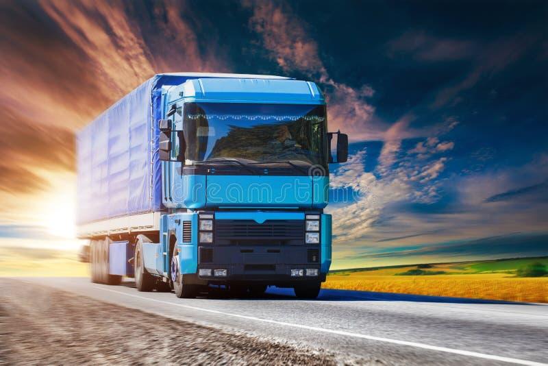 Blauwe vrachtwagen op weg stock foto's
