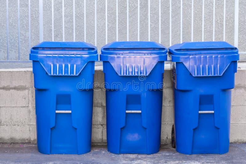 Blauwe vuilnisbakken tegen een muur stock afbeeldingen