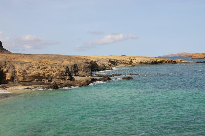 Blauwe waterbaai door de klip stock foto's