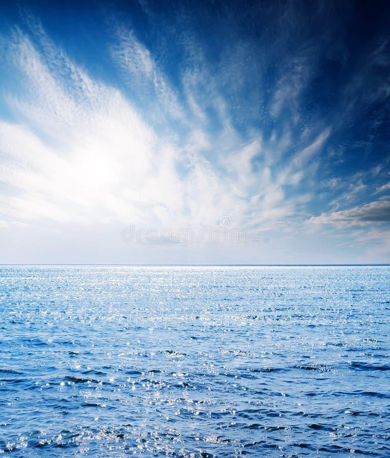 Blauwe wateroverzees en zon in lage wolken royalty-vrije stock fotografie