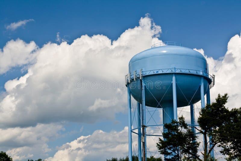 Blauwe watertoren onder bewolkte hemelen stock fotografie