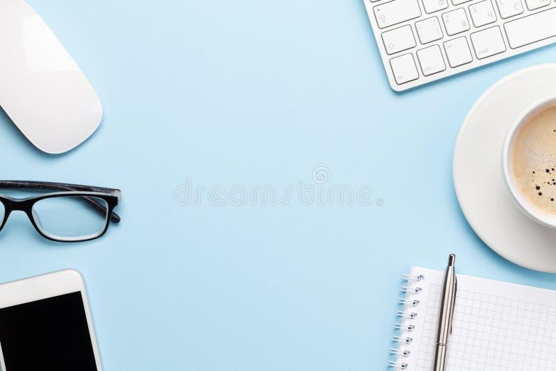 Blauwe werkplek met computer, smartphone en benodigdheden royalty-vrije stock fotografie