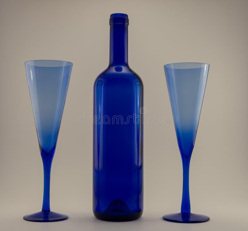 Blauwe wijnfles en twee champagneglazen royalty-vrije stock foto's