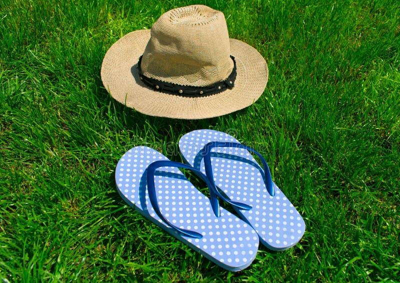 Blauwe wipschakelaars en de zomerhoed op groen gras stock fotografie