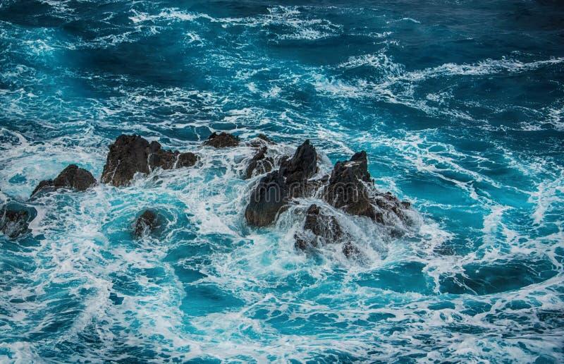 Blauwe woedende golven die op de rotsen verpletteren stock foto's
