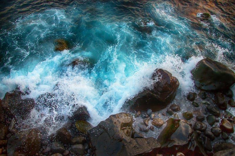 Blauwe woedende golven die op de rotsen verpletteren royalty-vrije stock afbeelding