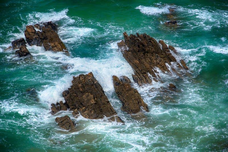 Blauwe woedende golven die op de rotsen verpletteren stock afbeelding