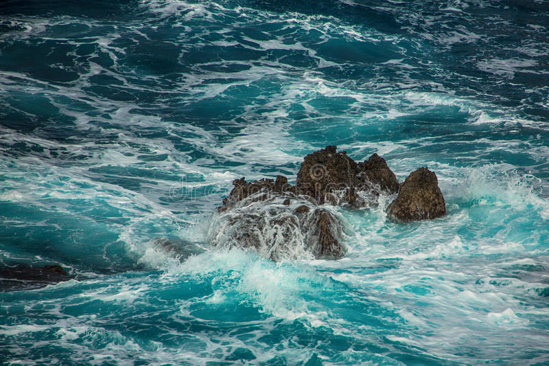 Blauwe woedende golven die op de rotsen verpletteren stock fotografie