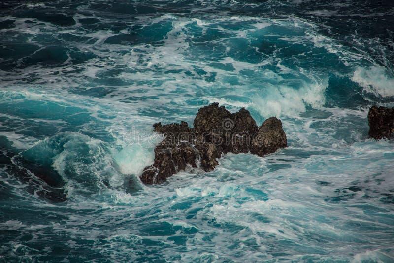 Blauwe woedende golven die op de rotsen verpletteren stock afbeeldingen