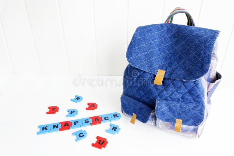 Blauwe zak met raadselbrieven op witte lijst Hand - gemaakte rugzak voor reizigers stock afbeeldingen