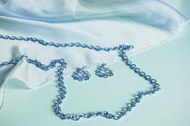 Blauwe zijde, gedrapeerde golven, zilveren ketting en oorringen, gekleurd beeld in pastelkleurblauw, luxetoebehoren voor vrouwen, royalty-vrije stock afbeelding