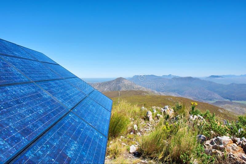 Blauwe zonnebeslagcellen en ontzagwekkende berg royalty-vrije stock afbeelding