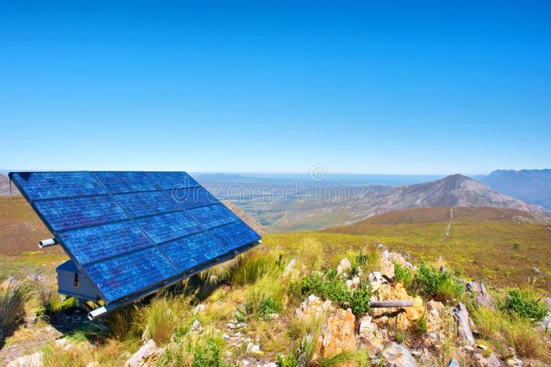 Blauwe zonnecellen tegen ontzagwekkend berglandschap royalty-vrije stock foto's