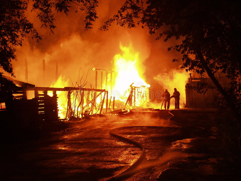 Blaze. At the night, burning building and 2 firemen stock image