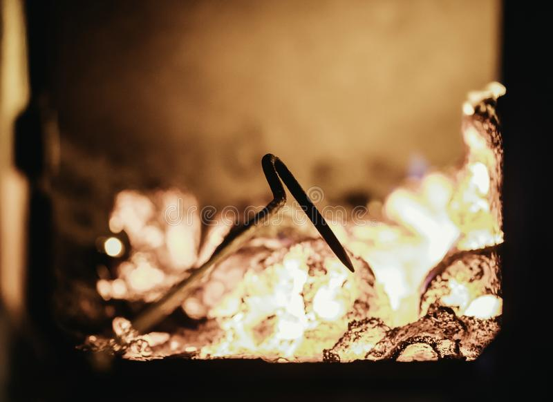 Blaze fire flame in oven, poking stick and sparks stock image
