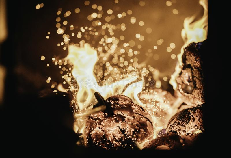 Blaze fire flame in oven, poking stick and sparks stock images