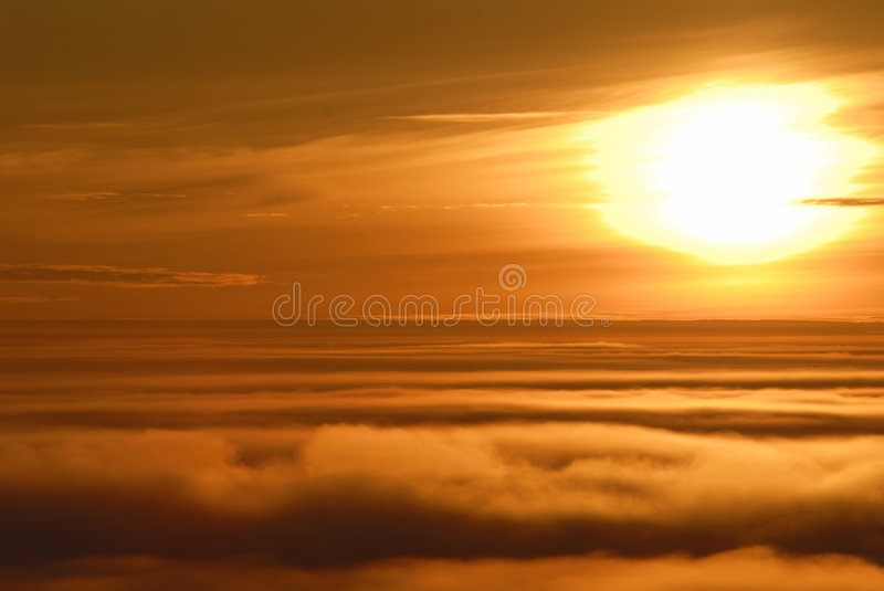 Blazing sun. Blazing rising sun. flight above clouds stock photography