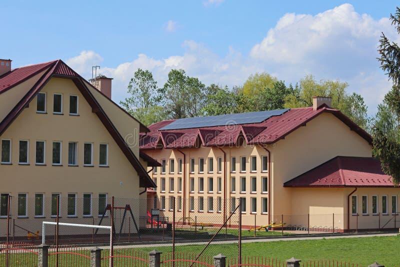 Blazkowa, Polen - kan 10, 2018: De schoolbouw met een voetbalgebied in de werf Het landschapsontwerp in stedelijk en landelijk en stock afbeelding