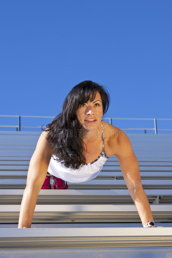 Bleachers Pushup. Pretty fitness woman doing a push up on bleachers royalty free stock photos
