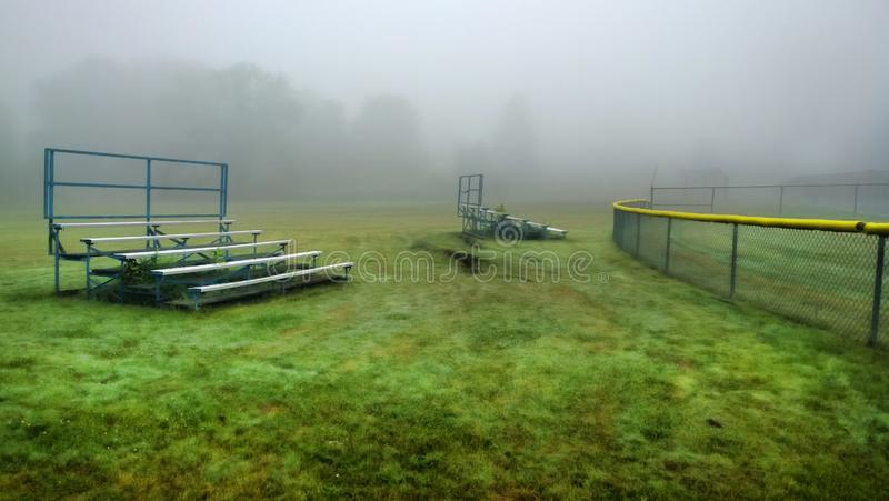 Bleachers in a school yard. Sports field on a foggy and rainy summer morning royalty free stock photography