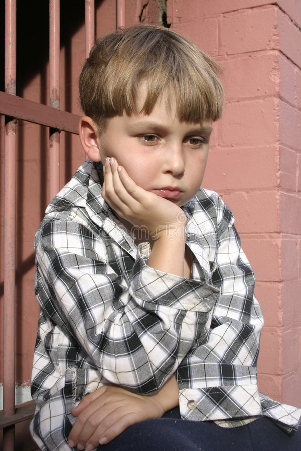 Bleak future. A helpless despondent child in mismatched clothing sits by a building stock images