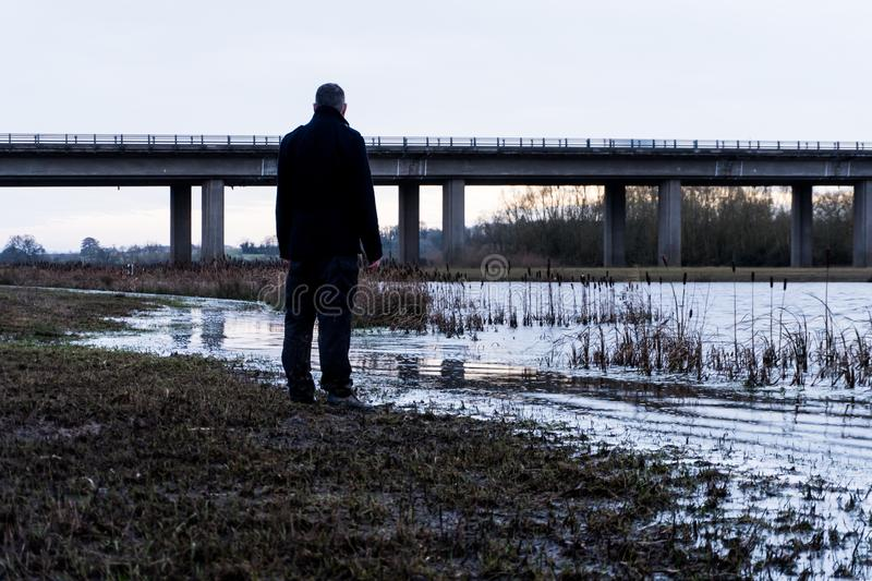 A bleak, moody, winter edit of a figure standing next to a lake, looking out to a motorway bridge, out of focus in the background.  stock images