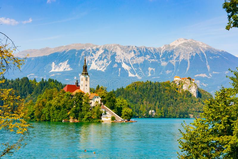 Bled Island and Bled Castle. Bled Island with Assumption of Mary church surrounded by the green waters of Lake Bled with castle cliff in the background, Upper stock image