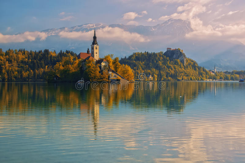 Bled lake and pilgrimage church with autumn mountain landscape background. Island on Bled lake and pilgrimage church of the Assumption of Mary with autumn stock images