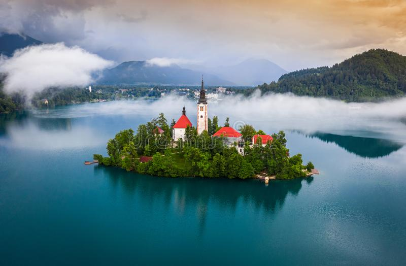Bled, Slovenia - Beautiful foggy morning at Lake Bled Blejsko Jezero with the Pilgrimage Church of the Assumption of Maria stock photography