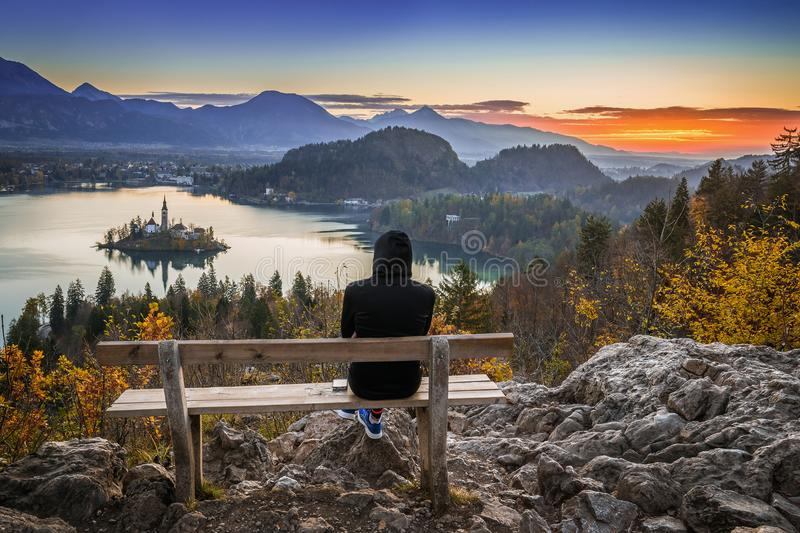 Bled, Slovenia - Runner woman relaxing and enjoying the beautiful autumn view and the colorful sunrise. Of Lake Bled sitting on a hilltop bench wearing black royalty free stock image