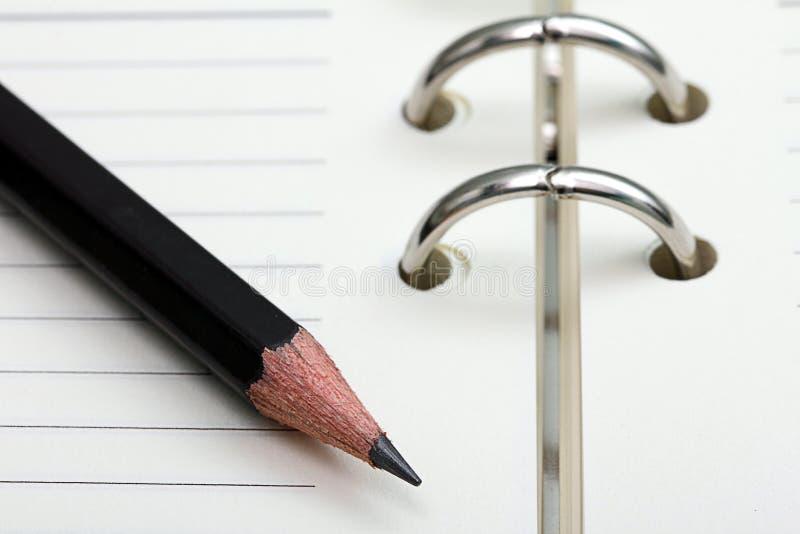 Bleistift auf Notizbuch stockbilder