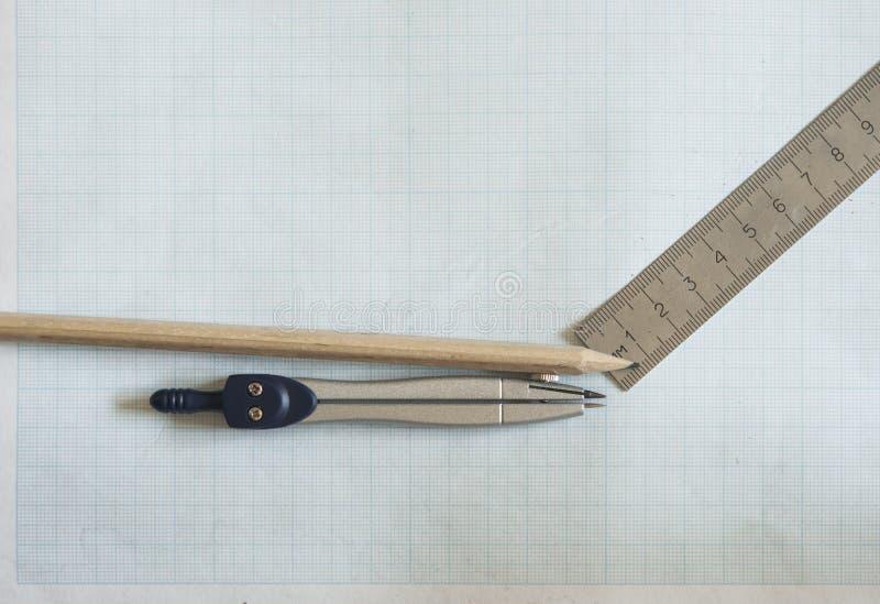 Bleistift, Kompass und Machthaber auf Zeichenpapiers- mit Maßeinteilunghintergrund lizenzfreies stockfoto