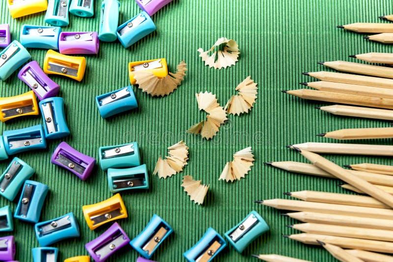 Bleistift mit Bleistiftspitzerbleistift auf grüner Wellpappe stockbild