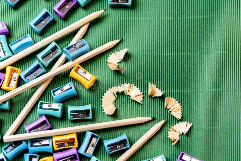 Bleistift mit Bleistiftspitzerbleistift auf grüner Wellpappe lizenzfreie stockfotos