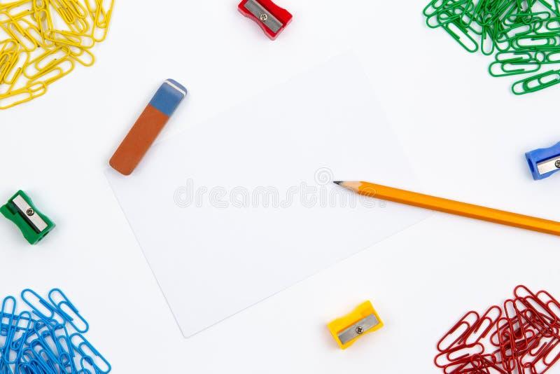 Bleistift, Radiergummi, Bleistiftspitzer, Büroklammern liegen in den verschiedenen Winkeln des Blattes auf einem weißen Hintergru lizenzfreie stockfotos