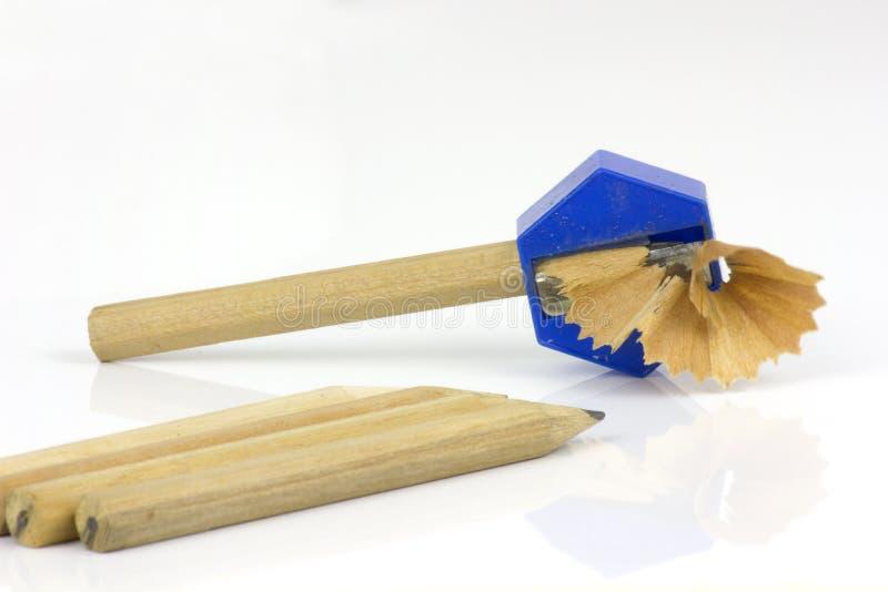 Bleistift und Bleistiftspitzer mit den Schnitzeln lokalisiert auf weißem Hintergrund lizenzfreie stockfotos
