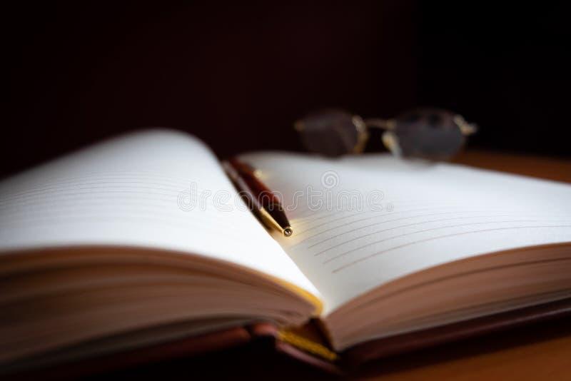 Bleistift und Lesebrille auf einer leeren Zeitschrift stockfotografie