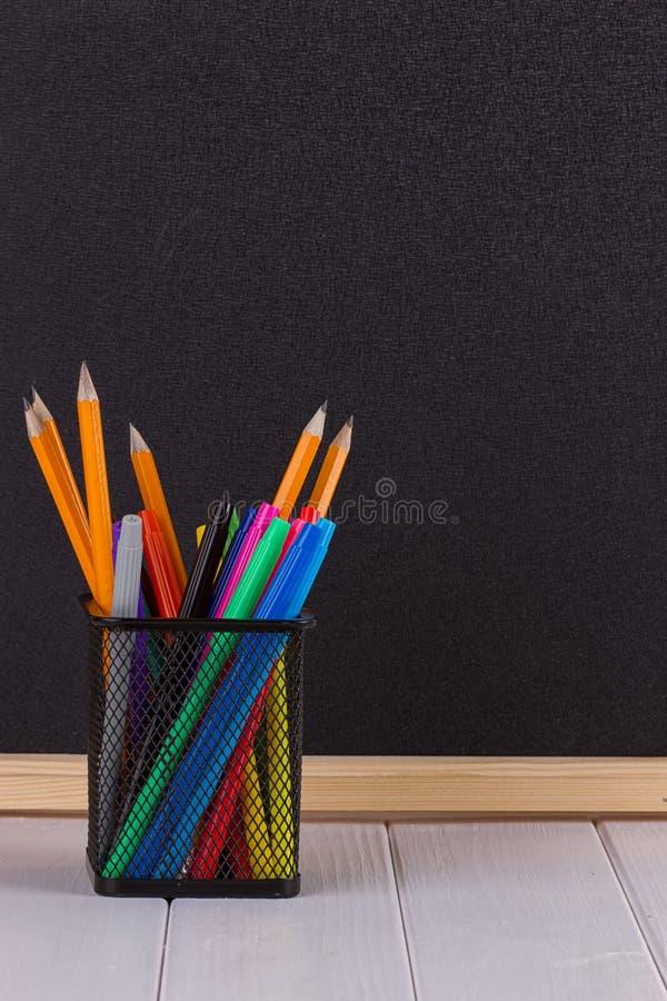 Bleistifte im Stand vor schwarzer Schulbehörde stockbilder