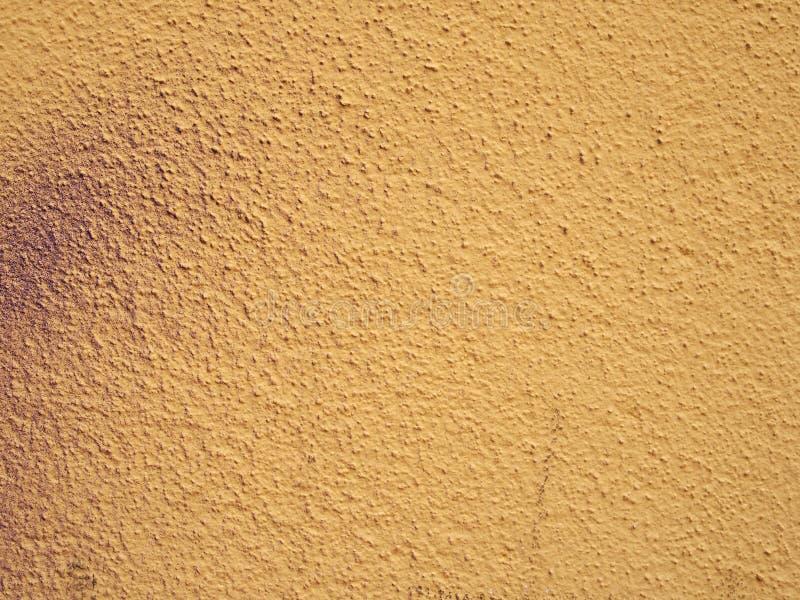 Blek kornig texturerad gul väggbakgrund med förslag av smutsig purpurfärgad sprutmålningsfärg arkivfoto