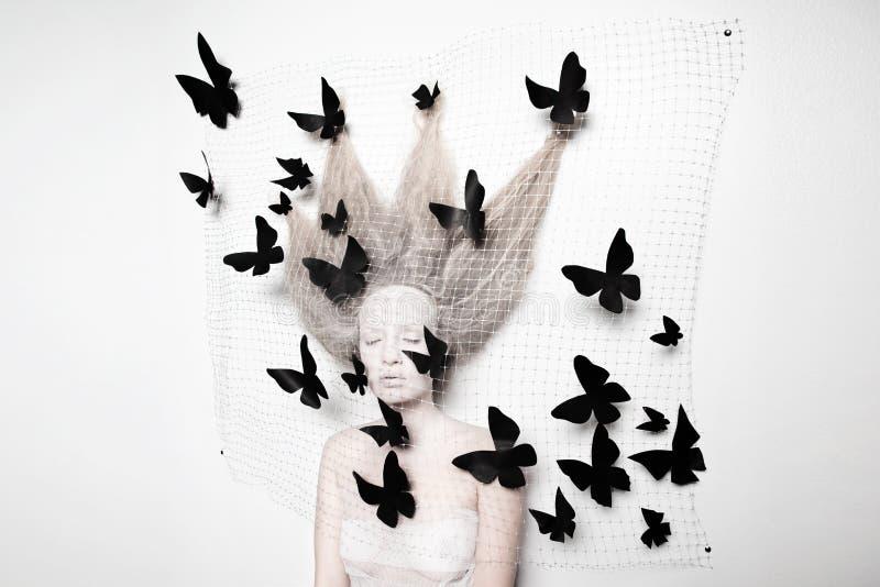 Blek kvinna i kokong med fjärilar arkivfoton