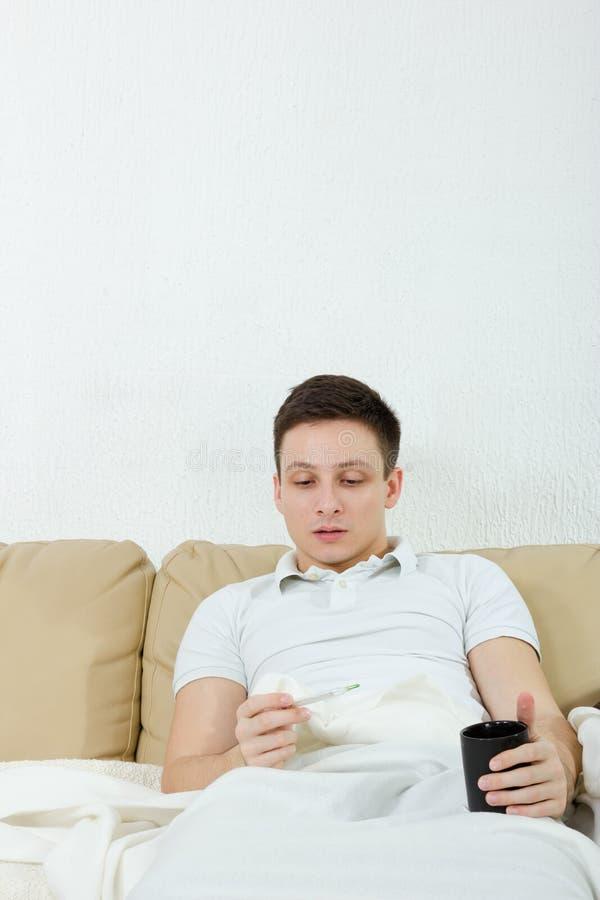 Bleke mensenzieken die thuis temperatuur en griep hebben royalty-vrije stock foto